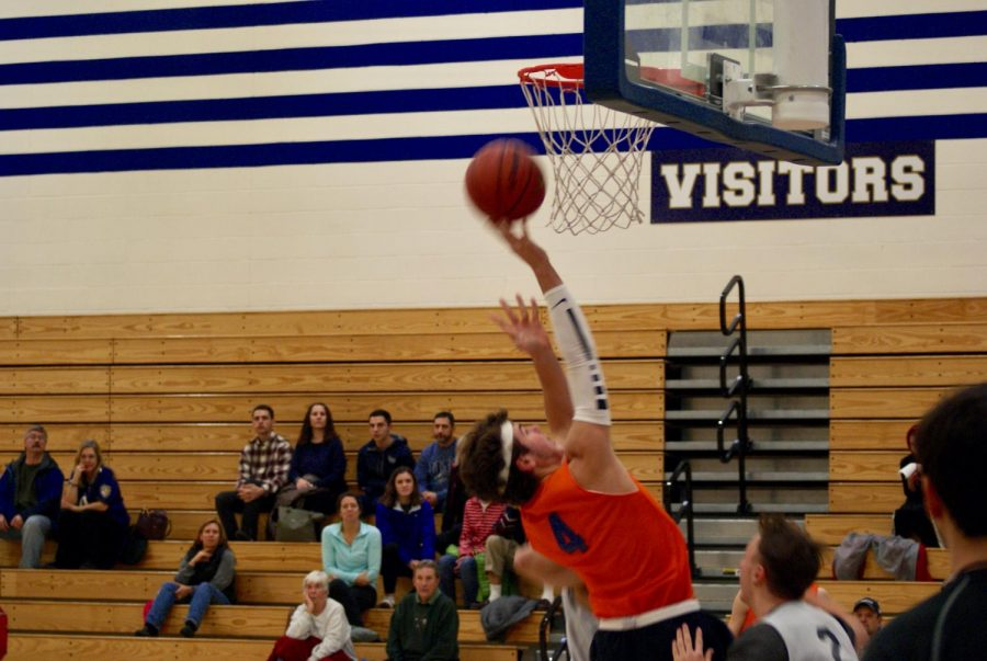 Alex Miller reaches up to the rim as he throws down.