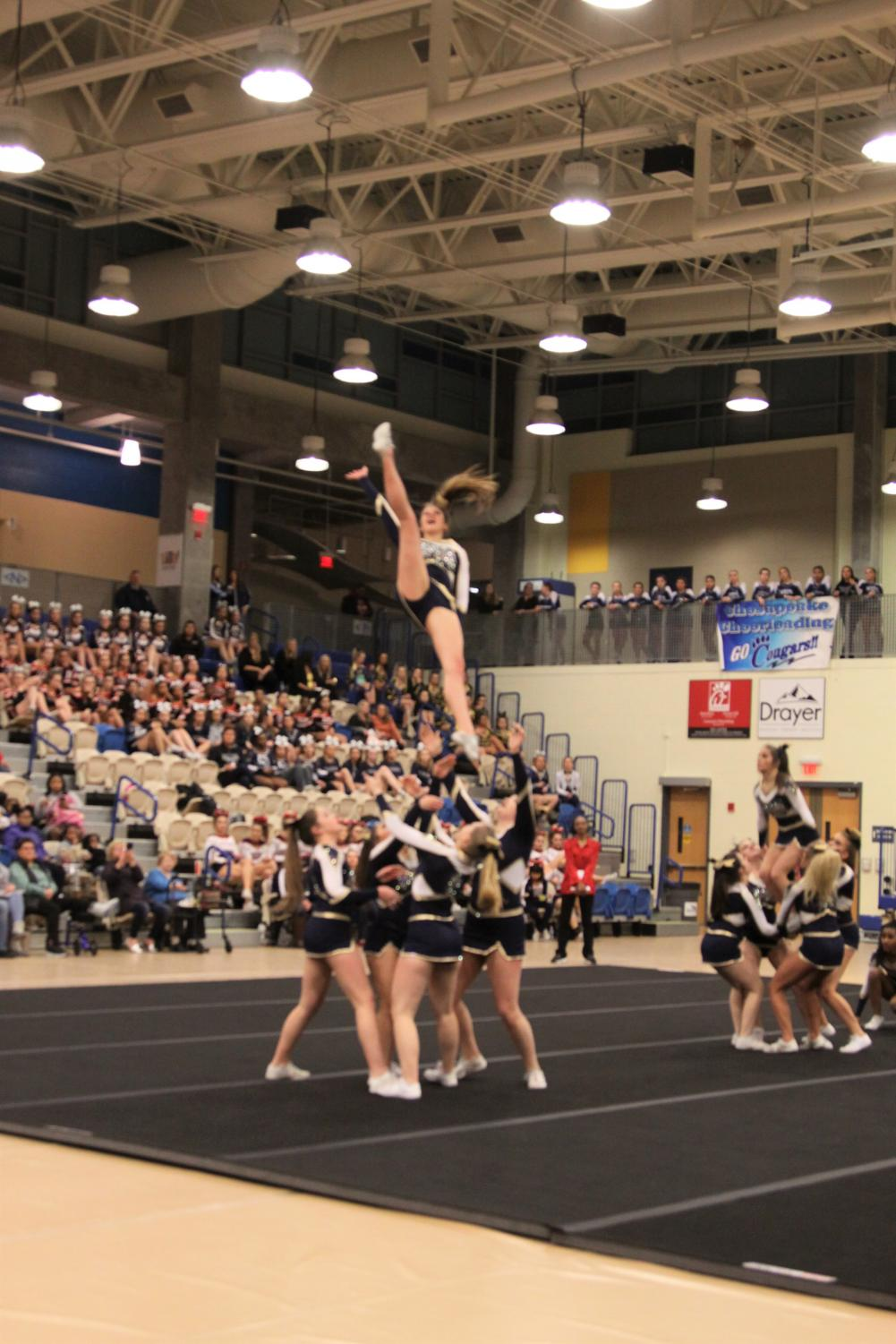 The cheer team doing a stunt at the state championship competition. The team placed tenth in their first ever appearance in states.