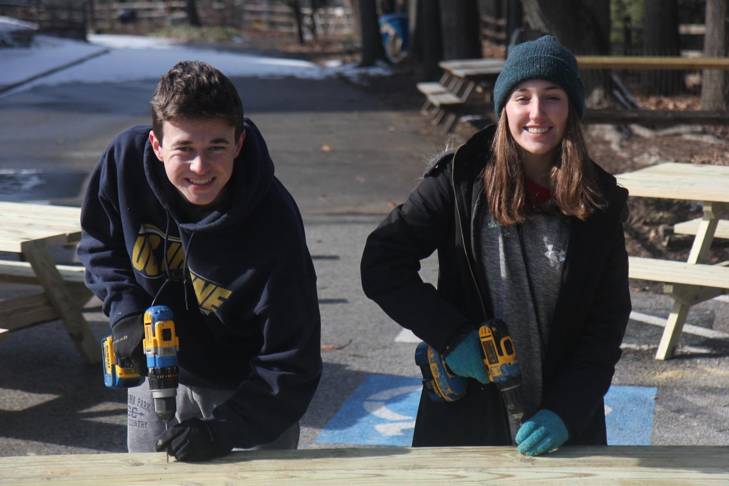 "Senior Lee and senior Melanie Reynolds are building a table top for one of the twenty-eight tables. Previously, Lee has participated in the build twice before, and this was Reynolds first year participating. ""Even though it was cold in the morning, we had donuts, coffee and bonfires to keep us warm while we hung out and built tables together,"" Lee said."