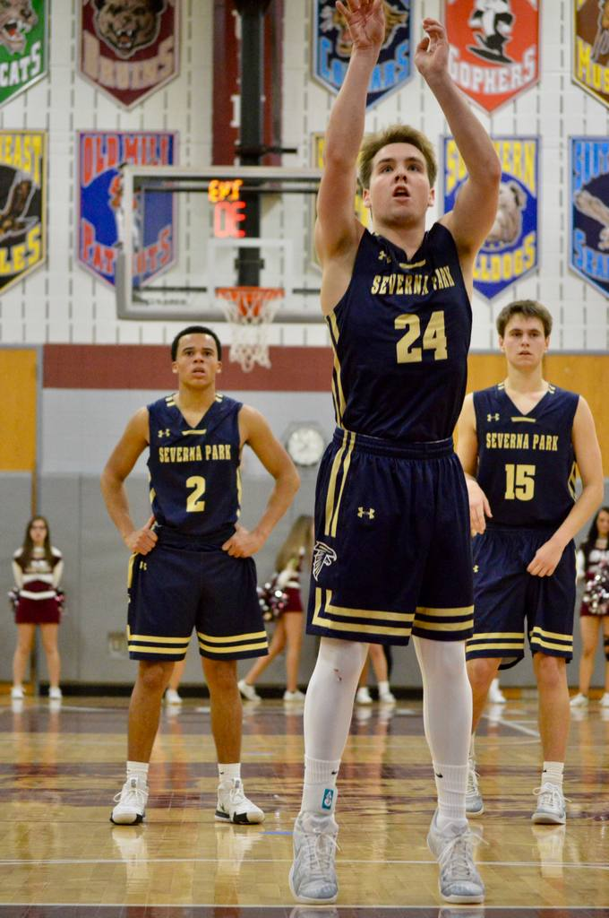 Josh Horgan shooting a free throw with teammates Colin Wolfe and Matt Simms looking on.