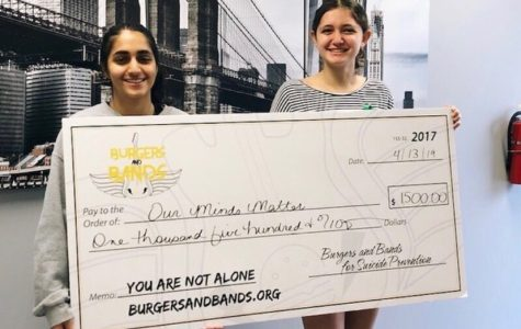 "Group co-founders Sabina Khan and Lauren Carlson hold a check for a 1,500 donation from local charity, Burgers and Bands. ""We are so excited to keep fighting the good fight with you,"" the group said."