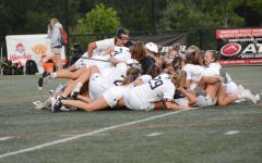 Girls lacrosse piles on top of each other after winning the 4A state title. The game was played at Paint Branch High School in Burtonsville, Maryland