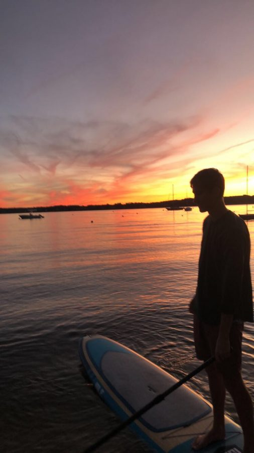 """Senior Bobby Davids paddleboards on the Severn River at sunset. He has had lots of time on the water to discover his true self and contemplate life. """"It's me on the outside, but it feels like I am controlled by  Morgan Freeman-like earthworms on the inside,"""" Davids said."""