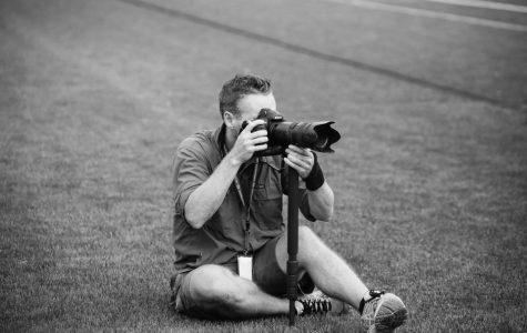 """Colin Murphy taking photos on a hill during a sporting event. Murphy enjoys just going to games and being in the atmosphere. """"I love sports, always have and always will,"""" Murphy said."""