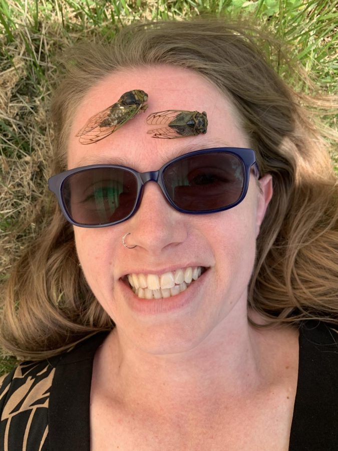 Ms. Mossa enjoys collecting things in nature like insects, rocks and fossils. In this picture she is posing with two cicadas from her collection. This spring Mossa said she plans on collecting as many cicadas as possible.