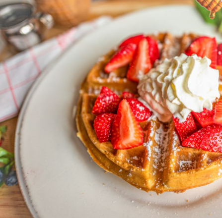 Big Belgian Waffles with powdered sugar, strawberries, and maple bourbon butter.